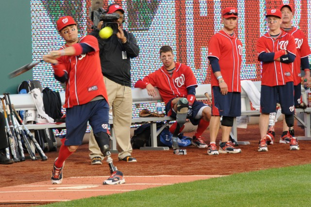 A wounded warrior swings at the pitch during the Amputee Softball Team exhibition game at Washington Nationals Stadium in Washington, D.C., April 3, 2012.