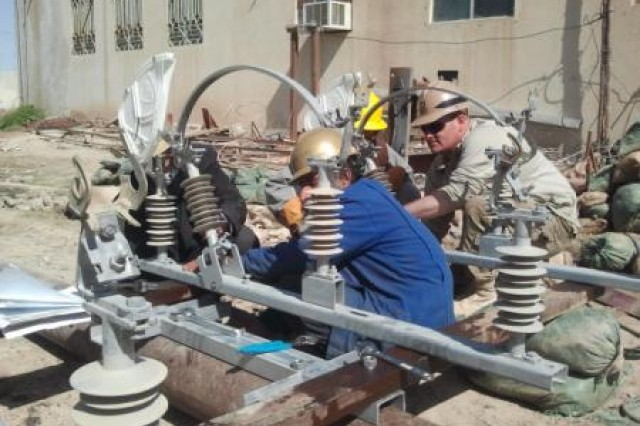 Afghan utility technicians and their U.S. Army counterpart, Staff Sgt. Scott Michael, assemble the air disconnect switch as part of the Sangin substation upgrade project in early March.
