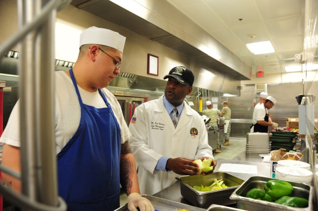During a visit with the Food Management Assistance Team out of Fort Lee, Va., Ron Bellamy, the team's food service systems analyst, show a few tricks of the trade to a food service specialist with 1st Brigade Combat Team's dining facility March 28.