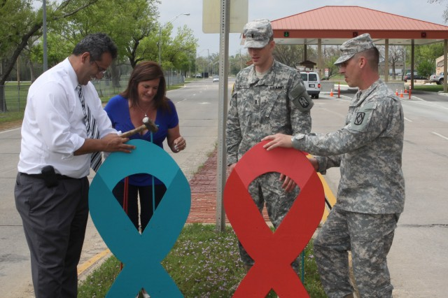 From left, Jay Khalifeh, ASAP program director, stands by with a hammer as Stephanie Armel, Training and Doctrine Command risk reduction coordinator, positions a stake to support a big ribbon as 1st Lt. Brian Caldwell, 214th Fires Brigade and Sgt. 1st. Class Michael Kimbel, 75th Fires Brigade hold their ribbon in place. April is alcohol abuse prevention month, represented by the red ribbon and sexual assault prevention month, represented by the teal ribbon. Both campaigns are supported by Fort Sill's ASAP and SHARP programs.