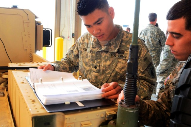 "Spc. Bryan Tran (left) and Spc. Dakota Lawrence, psychological operations specialists with the 307th Tactical Psychological Operations Company in St. Louis, Mo., review the operations manual for the RISO HC5500 print system during pre-deployment training in Dallas, Texas March 29, 2012. Tran and Lawrence helped train members of the 345th Tactical Psychological Operations Company on the system, known within the Army as the Psychological Operations Print System "" Light. The two were selected to be trainers because for most of the past year, the two worked on the system in Afghanistan and became experts in maintaining it in extreme conditions. A group of 345th TPC Soldiers will deploy to the Horn of Africa this summer and utilize the system to print everything from flyers to posters used to communicate with the local population (U.S. Army Photo By Lt. Col. Gerald Ostlund)"