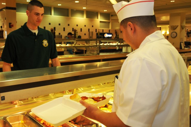 Spc. Jeremy Zavala, 529th Regimental Support Company food service specialist, 3d U.S. Infantry Regiment (The Old Guard), serves Pfc. Hyde Brett, Tomb Guard, Tomb of the Unknown Soldier, a hot breakfast to-go plate, April 1, at the Joint Base Myer-Henderson Hall, Va. dining facility. Brett was one of the first Soldiers to eat at the DFAC under the new management. (U.S. Army photo by Sgt. Luisito Brooks)
