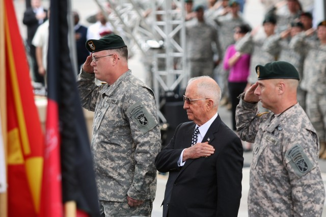 Col. B. Ashton Naylor (left), 1st Special Warfare Training Group (Airborne) Commander, Ross Perot (center) and Command Sgt. Maj. Channing Bell (right), 1st SWTG(A) Command Sergeant Major, honor the American flag during the playing of the national anthem during a Special Forces Regimental Day ceremony and qualification course graduation April 5 on Fort Bragg, N.C.