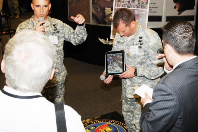 Lt. Col. Craig Unrath, deputy director of the Directorate of Simulations, and Maj. Lee Ambrose, commander A Company, 1st Battalion, 145th Aviation Regiment, explain the Army Learning Concept 2015 at the U.S. Army Aviation Center of Excellence Booth during the Army Aviation Association of America professional forum in Nashville, Tenn.