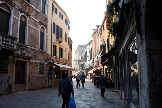 Venetians and tourists explore the shops along the pedestrian alleyways.