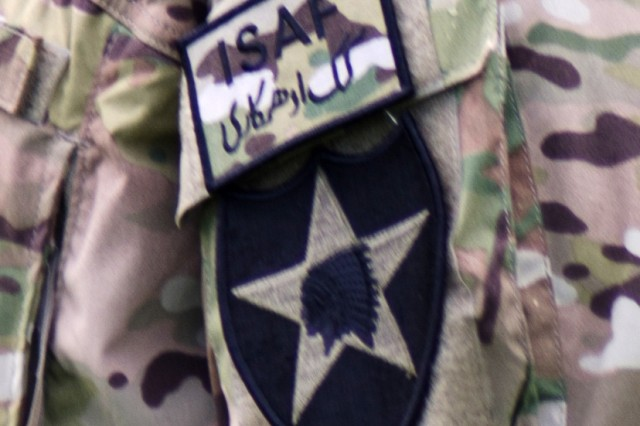 """JOINT BASE LEWIS-MCCHORD, Wash. (March 30, 2012) Af 2nd Bde., 2nd Inf. Div. Soldier wears an ISAF patch along with his own """"Lancer"""" insignia at Watkins Field, March 30. The Lancer Brigade cased its colors last week in preparation for a nine-month deployment to Afghanistan."""