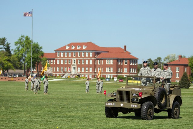 Cadet Command's headquarters sits in the background as Maj. Gen. Jefforey Smith and Maj. Gen. Mark McDonald and Lt. Gen. John Sterling Jr. ride in a vintage Jeep to review troops in formation for Friday's change of command.