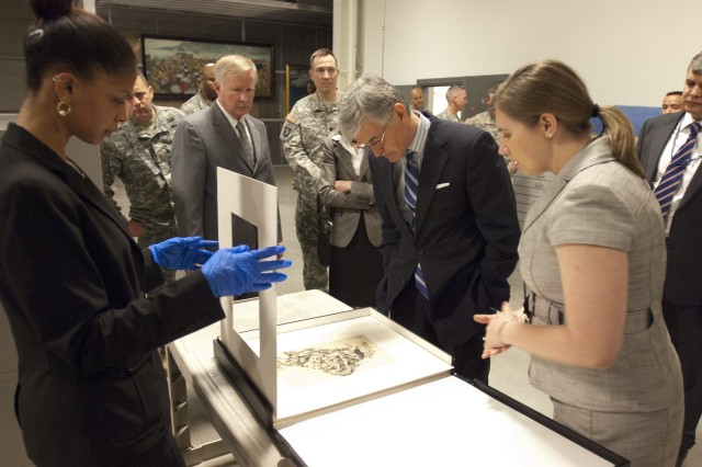 Secretary of the Army John McHugh inspects an original work of art while curator Sarah Forgey points out details of the piece during McHugh's visit to the Center of Military History Museum Support Facility, April 2, 2012, at Fort Belvoir, Va. (U.S. Army photo by Spc. John G. Martinez)