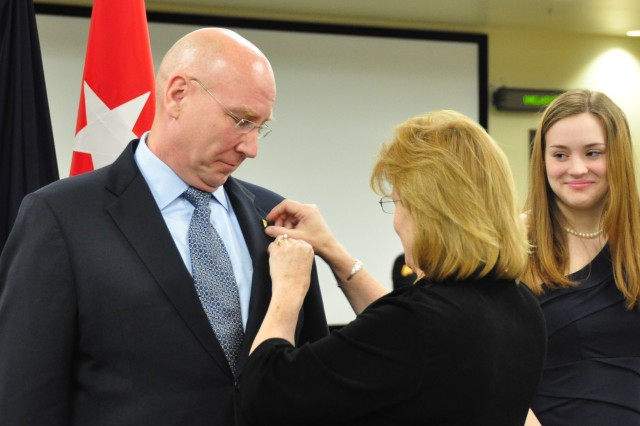 New Senior Executive Service (SES) member Guy C. Beougher watches as spouse Linda C. Beougher places the SES lapel pin on his suit coat, as daughter Mary  Beougher looks on, during a Senior Executive Service Induction Ceremony, April 9, 2012, at Fort Bragg, N.C. The ceremony was the first of its type since the command's headquarters relocated to Fort Bragg from Fort McPherson, Ga., in 2011