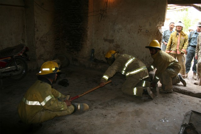 Firefighters from the Kandahar Fire Department in Afghanistan practice entering a smoke-filled room and searching for people trapped inside during a training opportunity with Soldiers from the 58th Military Police Company, attached to 1st Squadron, 10th Cavalry Regiment, 2nd Brigade Combat Team, 4th Infantry Division, held at their firehouse April 7, 2012. During the training, firefighters and Soldiers went over initial fire attack, using buddy teams to move to a fire and to egress from a fire, and they shared tips on best practices to include scene recovery and hose recovery.