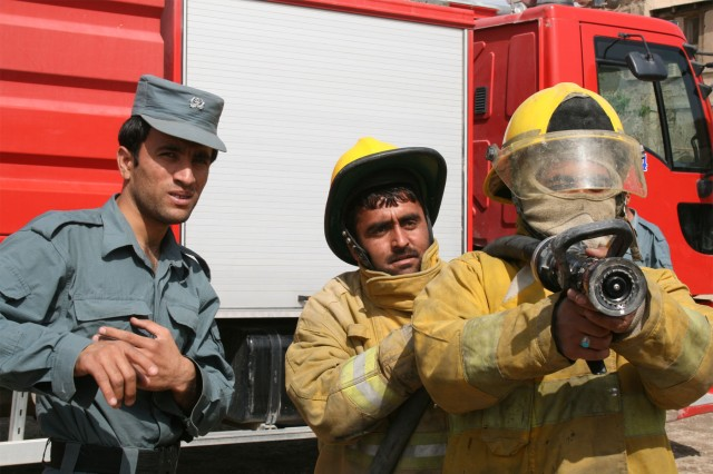 Firefighters from the Kandahar Fire Department practice proper hose handling techniques during a training class provided by Soldiers from the 58th Military Police Company, attached to 1st Squadron, 10th Cavalry Regiment, 2nd Brigade Combat Team, 4th Infantry Division, at their firehouse in Afghanistan, April 7, 2012. During the training, firefighters and Soldiers went over initial fire attack, using buddy teams to move to a fire and to egress from a fire, and they shared tips on best practices to include scene recovery and hose recovery.