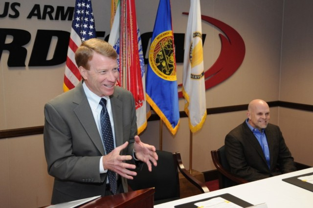 Joseph Wienand, acting deputy director, U.S. Army Research, Development and Engineering Command, shares a light-hearted moment with attendees at the April 9 Cooperative Research and Development Agreement signing ceremony. Chris Silva, chief executive officer, Allied Minds Federal Innovations, Inc., is seated. Wienand and Silva signed the agreement between Edgewood Chemical Biological Center and AMFI that will use technology transfer as a driver of economic growth.