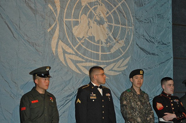 Soldiers, waiting for their cue to take the stage, stand before the United Nations Flag before the start of the 41st Annual Six Star Salute. 39 United States servicemembers, 39 Republic of Korea servicemembers, one Filipino Soldier and one Thai Soldier were honored for their outstanding work as a part of the Combined Forces working to keep South Korea safe.