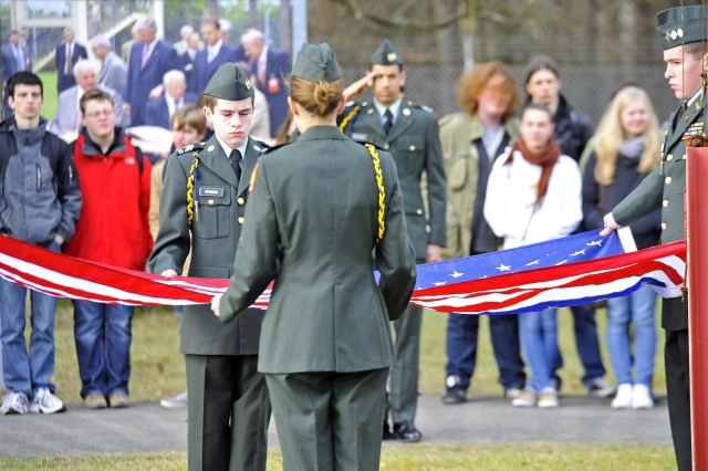 Members of the Wiesbaden High School's JROTC fold an American flag during the anniversary ceremony at the Point Alpha Memorial in Germany.