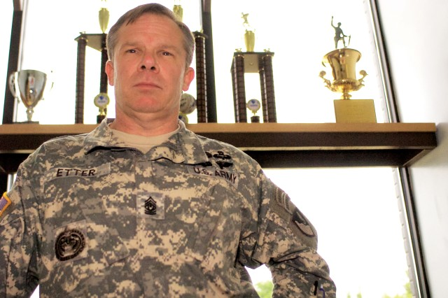 John Etter, command sergeant major of the 11th Engineer Battalion, poses in front of a collection of trophies the battalion has won in intramural sports over the past three years. On May 28, Etter will become the command sergeant major of the 130th Engineer Brigade   at Schofield Barracks, Hawaii.