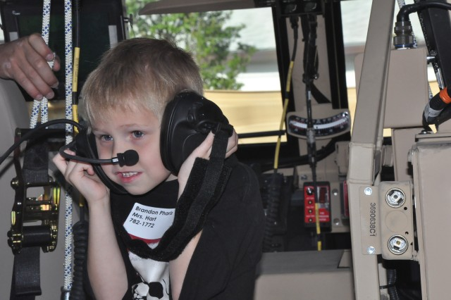 Brandon Pharis, 5, tries the microphone and headset equipment inside an Army vehicle during a Monday morning tour of Fort Jackson's Army Basic Combat Training Museum.