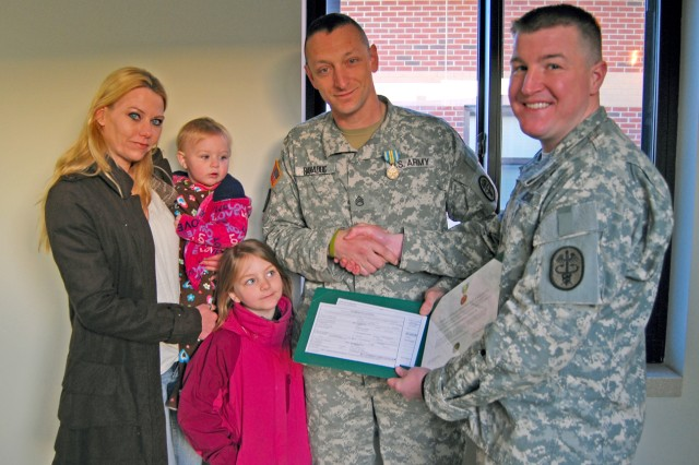 Staff Sgt. Gheorghe Banaduc Jr., center, gathers with his wife Jessica and children for a photo with 1st Lt. Matthew B. Robinson, commander of B Company, 3-85th Warrior Transition Unit, after receiving the Military Outstanding Volunteer Service Medal for serving as an emergency medical technician and firefighter with a local fire department.