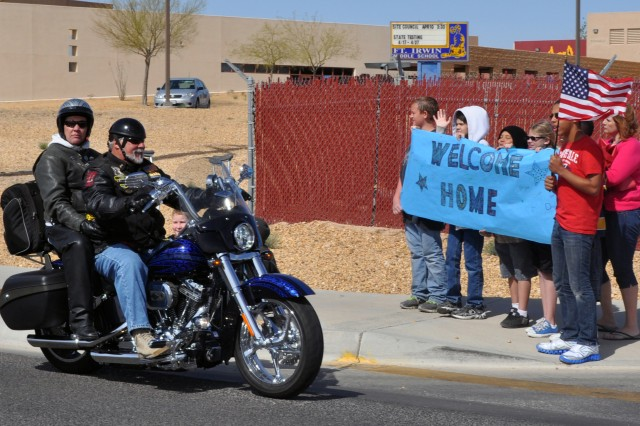 Fort Irwin Middle School students wave signs and flags as veterans ride past them on Normandy Road during the Vietnam-era Veterans Welcome Home ceremony motorcycle parade April 4, 2012, at Fort Irwin, Calif.