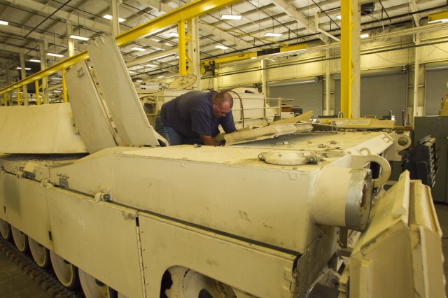 In this 2011 file photo, Steven Homesley, an Anniston Army Depot heavy mobile equipment mechanic, disassembles an M1A2 Abrams tank to be repaired and upgraded for the Royal Saudi Land Forces.