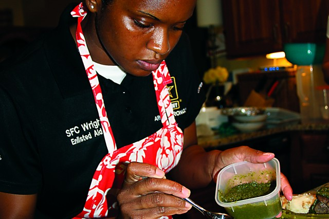 """Sgt. 1st Class Latovia Wright puts the finishing touches on a dish she prepared for an official function for Maj. Gen. Alan R. Lynn, U.S. Army Signal Center of Excellence and Fort Gordon commander, and his wife Brook, at Quarters 1 on post.  Wright, the general's enlisted aide/chef, won the Bronze medal in the enlisted aide category at the 37th Annual Military Culinary Arts Competition held Feb. 29 """" March 7 at Fort Lee, Va."""