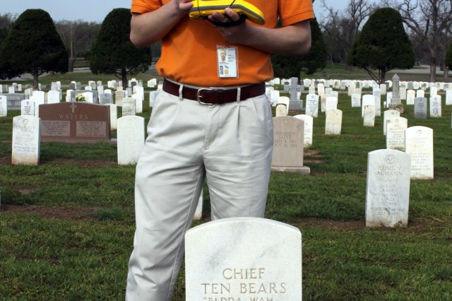 Aaron Peterson, Geospatial Information Systems specialist, Directorate of Public Works, holds a hand-held GPS unit over the headstone of Comanche Chief Ten Bears to mark the exact location at Fort Sill, Okla. Peterson has been working on the mapping project to mark every gravesite in Fort Sill's cemeteries. The main post cemetery was established when Fort Sill was founded in 1869.