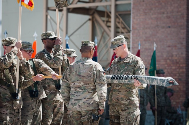 Lt. Col. James Davis, commander of the 1st Infantry Division Headquarters and Headquarters Battalion and Task Force Defender, prepares to unfurl his unit's colors in a transfer of authority ceremony on Bagram Airfield, Afghanistan, April 12.