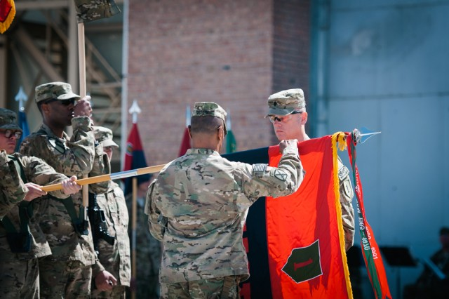 Lt. Col. James Davis, commander of the 1st Infantry Division Headquarters and Headquarters Battalion and Task Force Defender, unfurls his unit's colors in a transfer of authority ceremony on Bagram Airfield, Afghanistan, April 12.
