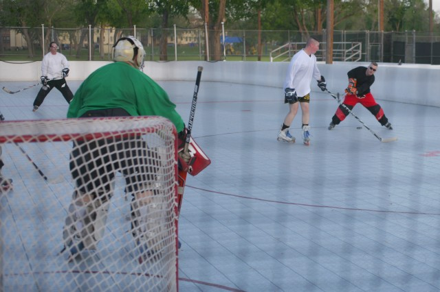 FORT SILL, Okla. (April 12, 2012) -- James Lucas sends a wrist shot toward the goal, guarded by goalie Josh Freggoe at the outdoor roller hockey rink on Fort Sill April 5. Inline hockey enthusiasts play Tuesdays and Thursdays from 6:30-8:30 p.m. at the rink near Patriot Club and welcome anyone interested in playing.