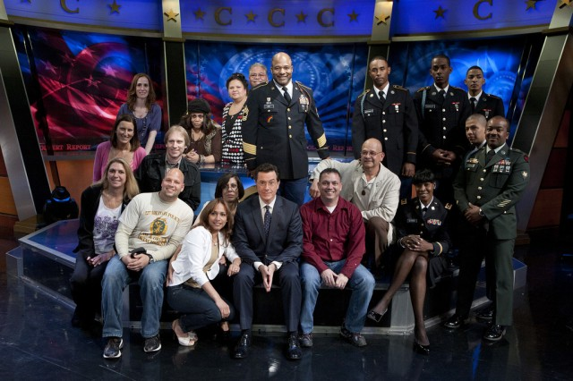 Soldiers and Family members of the 727th Military Police Law and Order Detachment, the 369th Sustainment Brigade and 1st Battalion, 69th Infantry Regiment gather around Stephen Colbert, host of The Colbert Report after his conversation with first lady Michelle Obama, on the first anniversary promoting Joining Forces,  a national initiative led by the first lady and Dr. Jill Biden that mobilizes all sectors of society to give our service members and their families the opportunities and support they have earned.