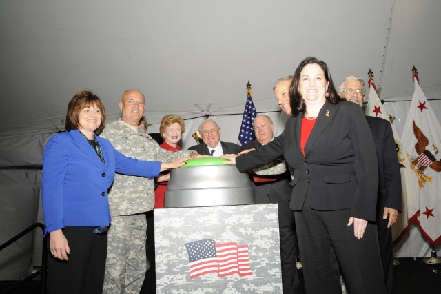Dignitaries press the button opening the door to the new Ground Systems Power and Energy Laboratory in Warren, Mich., April 11, 2012.  On right is Katherine Hammack, assistant secretary of the Army for Installations, Energy and Environment.  On the left is Army Materiel Command Chief Technology Officer Grace Bochenek, and behind her is Maj. Gen. Kurt Stein of the U.S. Army Tank and Automotive Command.