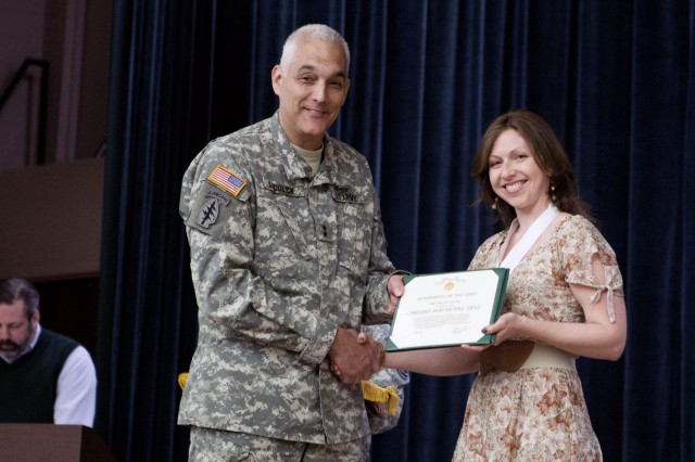 Nicole Young is awarded the Commander's Award for Public Service by Maj. Gen. Bennet S. Sacolick, commanding general of the U.S. Army John F. Kennedy Special Warfare Center and School, for her dedication and support in helping to form a Family readiness group for the Families of Special Forces Qualification Course students. Young's husband is a student in the course. A ceremony honoring SWCS Family volunteers was held April 12 on Fort Bragg, N.C.