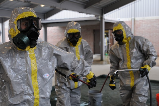 "JOINT BASE LEWIS-McCHORD, Wash. ""  Specialist Jordan Durand (left) goes through a decontamination wash while wearing a class-C protective suit during hazardous material operations training April 11. Soldiers of the 547th Area Support Medical Company are training to take part in the Defense Support of Civil Authorities mission in October. (U.S. Army photo by Sgt. Mark Miranda)"