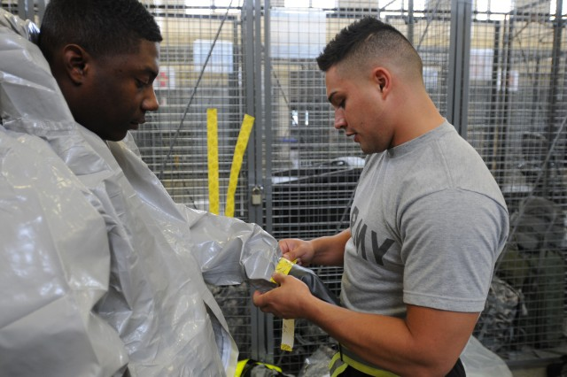 "JOINT BASE LEWIS-McCHORD, Wash. ""  Specialist Jordan Durand (right) helps Pfc. Darian Fayson seal his gloves to a class-C protective suit during hazardous material operations training April 11. Both Soldiers are part of the 547th Area Support Medical Company, currently training to take part in the Defense Support of Civil Authorities mission in October.  (U.S. Army photo by Sgt. Mark Miranda)"