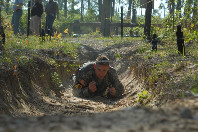 Capt. Josh Bobbitt, from Team 43, 4th Ranger Training Battalion, crawls under a low-wire obstacle on the Darby Queen obstacle course during day one of the Best Ranger Competition at Fort Benning, Ga., April 13. Photo by Staff Sgt. Thaddius S. Dawkins II, 49th Public Affairs Detachment (Airborne).
