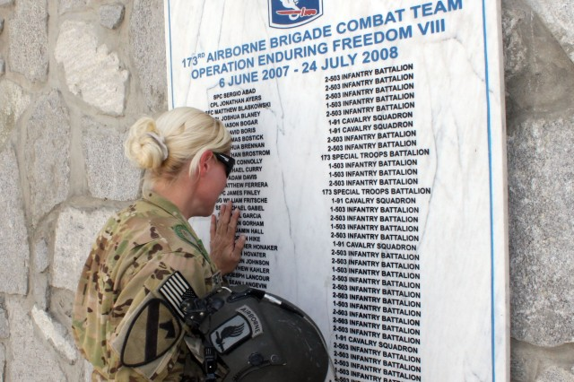 KUNAR PROVINCE, Afghanistan -- Staff Sgt. Charlene Navarrette, from Havelock, N.C., a flight medic assigned to Company C, Task Force Lobos, 1st Air Cavalry Brigade, 1st Cavalry Division, touches a memorial stone at Forward Operating Base Fenty April 9 that bears the name of her brother Spc. Christopher Honaker who was killed in action July 5, 2007 in Afghanistan while assigned to the 173rd Brigade Combat Team. Navarrette visited Combat Outpost Honaker-Miracle April 10, which is named after her brother and Pfc. Joseph Miracle. (U.S. Army photo by Staff Sgt. Joe Armas, 1st ACB, 1st Cav. Div. Public Affairs)