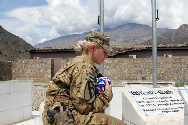 KUNAR PROVINCE, Afghanistan -- Staff Sgt. Charlene Navarrette, from Havelock, N.C., a flight medic assigned to Company C, Task Force Lobos, 1st Air Cavalry Brigade, 1st Cavalry Division, holds a flag from the 173rd Brigade Combat Team as she looks down at a memorial stone at Combat Outpost Honaker-Miracle' memorial stone that bears her brother's name April 10. The memorial is dedicated to Soldiers who died while serving in the Pech Valley. The outpost is named after Navarrette's brother, Spc. Christopher Honaker, and Pfc. Joseph Miracle who were killed in action July 5, 2007 in Afghanistan while assigned to the 173rd BCT. (U.S. Army photo by Staff Sgt. Joe Armas, 1st ACB, 1st Cav. Div. Public Affairs)