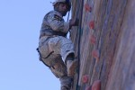 Army Sgt. 1st Class Vince Castellanos climbs the rock wall on the tri-tower during the Best Ranger Competition
