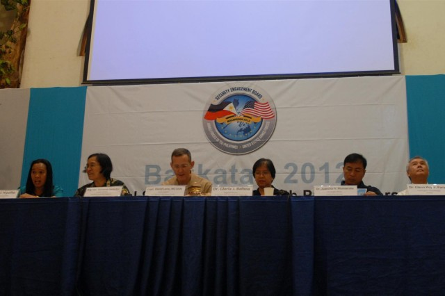 "PUERTO PRINCESA, Palawan, Republic of the Philippines "" Left to right: Helen J. Hipolito, project development specialist, Office of Health, USAID; Philippine Col. Maria Imelda Perez Dalupang, executive officer, Office of the Surgeon General; U.S. Navy Capt. David A. Lane, force surgeon, U.S. Marine Corps Pacific; Philippine Dr. Gloria Balboa, regional director, Center for Health Development, Region IV-B; Philippine Dr. Juancho V. Monserate, city health officer, Puerto Princesa City and Dr. Glenn Roy V. Paraso, Luzon senior area manager, PRISM2 collect their notes and thoughts before a medical symposium that brought Philippine and U.S. medical and veterinary professionals together to exchange knowledge and ideas in Puerto Princesa, Palawan, Republic of the Philippines on April 10. The medical symposium is part of the humanitarian civic assistance (HCA) portion of Exercise Balikatan 2012 (BK12), which officially starts on April 16, with the HCA portion of the exercise that started earlier on March 12 with engineering projects which consisted of building two-room classrooms at five schools within the Puerto Princesa area. The construction projects are now over 50 percent complete and are expected to be completed by April 27, 2012.  BK12, in its 28th iteration,  is an annual bilateral training exercise between the Armed Forces of the Philippines and the U.S. military to enhance interoperability between the two partner nations. (U.S. Army Photo by 1st Lt. Ray K. Ragan, Combined Joint Civil-Military Operations Task Force Public Affairs Officer)"