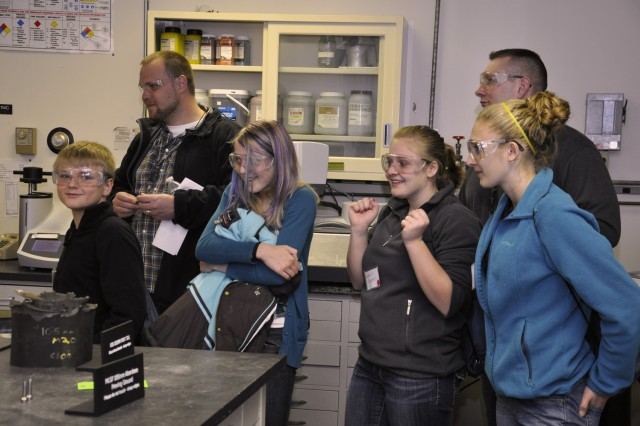 Students react to the popping sound from a piece of metal that was undergoing fatigue testing.