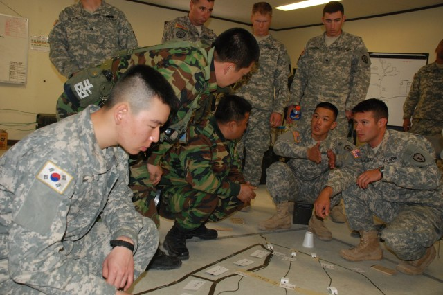 RODRIGUEZ TRAINING RANGE, South Korea - Pfc. Seung Ho Han (second from the right), a chemical specialist with 1st Battalion, 21st Infantry Regiment, translates a rehearsal discussion between 1st Lt. Eli Gaylor (right) and Master Sgt. Jan Sup Kung (center), of the 3rd Tank Company, 56th Battalion, 9th Regiment, April 12, in preparation for a combined U.S. and Republic of Korea army live-fire exercise. The training event was part of Foal Eagle 2012, an annual combined training exercise between the U.S. and Republic of Korea armies, which focuses on strengthening partnerships and war-fighting skills.