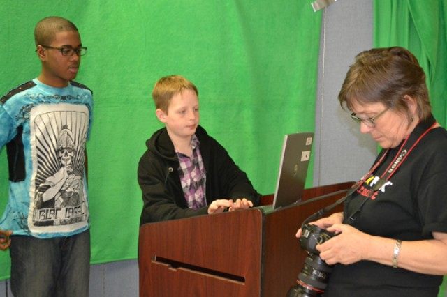 "Evan Clark, center, and another participant assist Linda Dennis, program manager, is setting up the green screen for a film making module. The module includes a ""one-minute claim to fame"" clip for each student. Clark's film, describing the life of a military child as ""unpredictable,"" will be presented to Congress in mid-April."