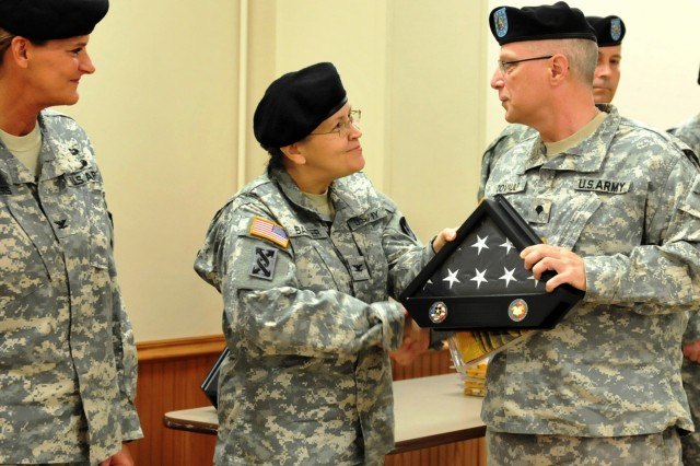 """Col. Vicki Baxter, Army Sustainment Command """" Army Reserve Element commander, presents Spc. Kris Covault with a folded United States Flag during the April 15 Welcome Home Warrior-Citizen Soldier ceremony, held at Heritage Hall, Rock Island Arsenal, Ill. (Photo by Megan McIntyre, ASC Public Affairs)"""