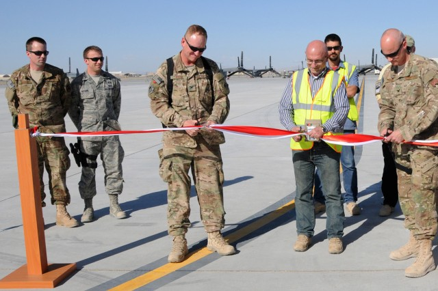 Air Force Col. Benjamin Wham, Afghanistan Engineer District South commander (left), Labib Bardawil, Contrack Inc. area manager (center), and Air Force Col. Sam Grable, 451st Air Expeditionary Mission Support Group commander, cut the ceremonial ribbon that marks the completion of the 4th phase of  a Kandahar Airfield expansion in southern Afghanistan, April 10, 2012.