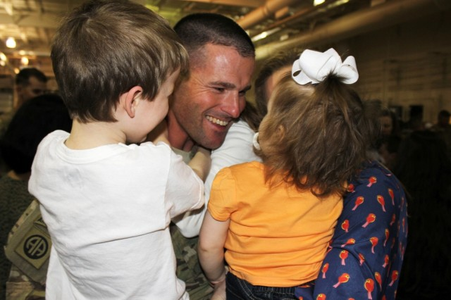 Maj. Kenneth Bath and his children share a tender embrace April 13 during a reception ceremony at Fort Wainwright, Alaska. Bath returned home to Fort Wainwright after completing a 12-month deployment to Afghanistan with the 1st Stryker Brigade Combat Team, 25th Infantry Division.