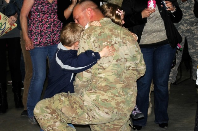 Lt. Col. John McMurray, Commander of the 25th Brigade Support Battalion, 1st Stryker Brigade Combat Team, 25th Infantry Division, shares a tender moment with his family during a reception ceremony April 9 at Fort Wainwright, Alaska.