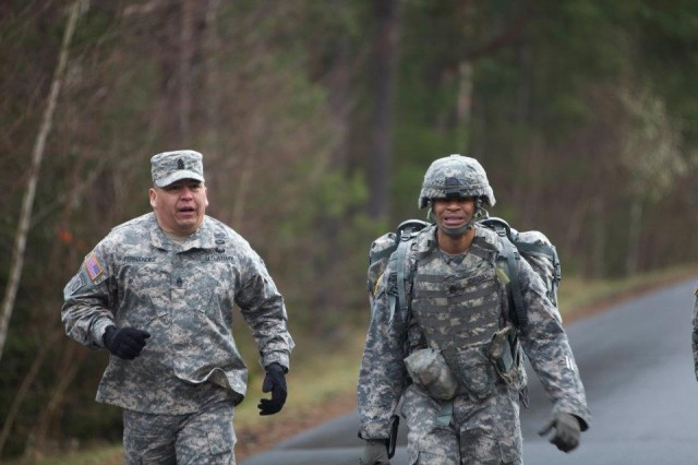 Command Sgt. Maj. Bentura Fernandez, 409th Contracting Support Brigade, pushes Staff Sgt. Booker Jordan, contracting specialist, 903rd Contingency Contracting Battalion, to finish the 12-mile forced road march. Jordan won the 409th NCO of the Year competition and now moves on to the Army Contracting Command - level competition at Camp Bullis in San Antonio, Texas.