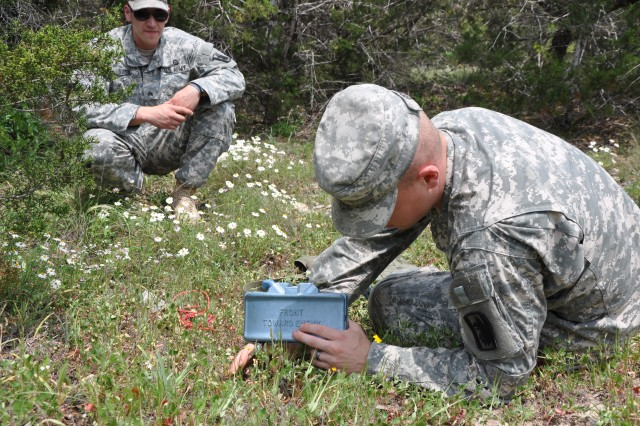 Under the watchful eye of a 470th Military Intelligence Brigade observer, a Noncommissioned Officer of the Year competitor goes through the procedures of arming a Claymore mine on Camp Bullis April 10. (U.S. Army photo by Sgt. Qaasim Jenkins)