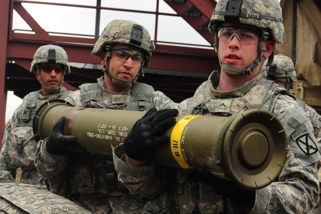 Soldiers with 1st Brigade Combat Team's D Company, 1st Battalion, 87th Infantry Regiment carry a Tube-launched, Optically-tracked, Wire-guided missile to the Improved Target Acquisition System before firing it down range April 10 in the Fort Drum training area.