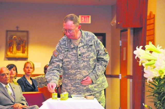 Chaplain (Lt. Col.) James King, deputy garrison chaplain and senior Protestant pastor, lights a candle in honor of lost lives during Fort Belvoir's cultural observance of Holocaust Days of Remembrance Tuesday. Photo name: 0491holocaust.jpg