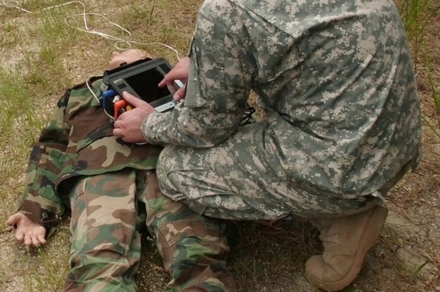 The JPC-1 is charged with developing medical training and simulation tools to improve combat medicine.  Here, a Soldier demonstrates a point of injury physiological monitor; this device is capable of sending real-time physiology data about a patient through the existing secure communications system.